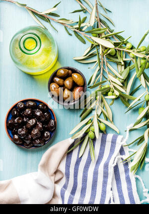 Two bowls with pickled green and black olives, olive tree sprigs, fresh homemade oil over blue Turquoise background - Stock Photo