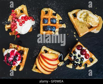 Warm belgian homemade waffles with fresh garden berries, fruit and ice cream on dark slate stone background - Stock Photo