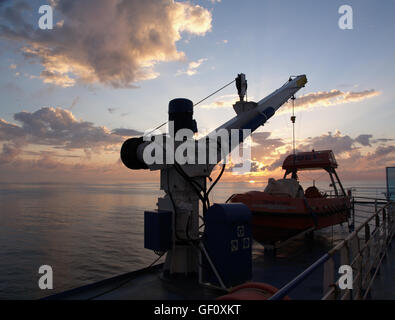 Sunset from main deck of Minoan Lines Ferry Ship Cruise Olympia Ancona, Italy to Igoumenitsa Greece Lifeboat in - Stock Photo