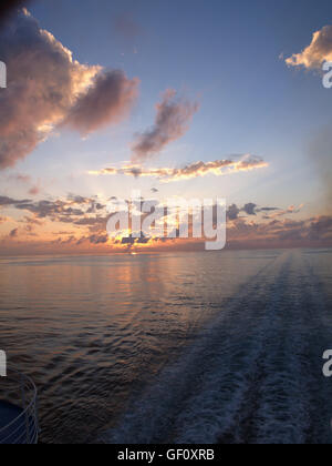 Sunset and wake from main deck of Minoan Lines Ferry Ship Cruise Olympia during journey from Ancona, Italy to Igoumenitsa - Stock Photo