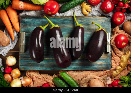 Fresh big eggplants close-up among frame made from ripe vegetables on wooden background. Top view. Aubergines, cabbage, - Stock Photo
