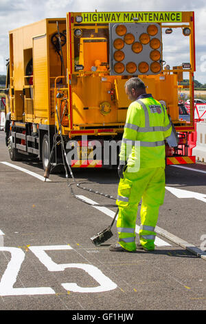 City Council motorway maintenance roadworkers paint white lines on streets. Chapter 8 Traffic Management systems - Stock Photo