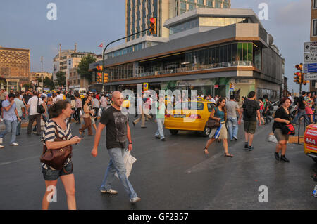 Pedestrians and taxis on Taksim square in central Istanbul.    This is a partial view of the square, on its side - Stock Photo