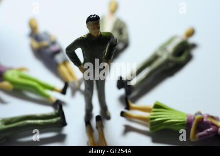 Miniature man Man standing over lying figures on ground - Stock Photo