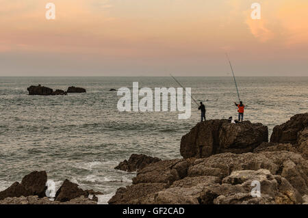 Two men fishing on a large rock on the north coast of Spain, Noja, Cantabria, Europe - Stock Photo