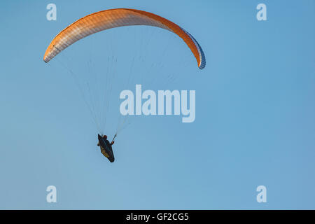 Paraglider in flight with colourful wing, canopy against blue sky. Views from the viewpoint of Pena Cabarga, Cantabria, - Stock Photo