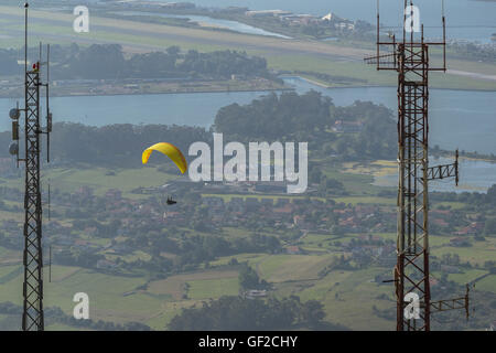 Paraglider in flight with colourful wing, canopy. Views from the viewpoint of Pena Cabarga, Cantabria, Spain. - Stock Photo