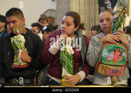 Worshipers with statues and other articles of devotion to Saint Jude Thaddeus, assist at a Mass on the saint's feast - Stock Photo