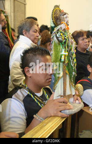 Worshipers with statues and other articles of devotion to Saint Jude Thaddeus, assist at a Mass in Mexico City. - Stock Photo
