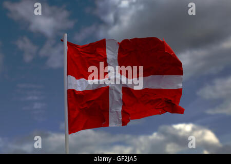A crumpled and torn paper Dannebrog flag, the Danish flag against dark clouds. Close to being the happiest people? - Stock Photo