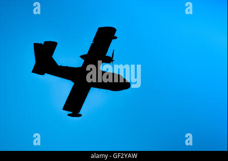 Silhouette of a propeller plane on a blue sky background. - Stock Photo