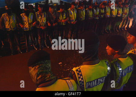 Cilacap, Indonesia. 29th July, 2016. Police officers stand guard when an ambulance (not in frame) carrying the body - Stock Photo