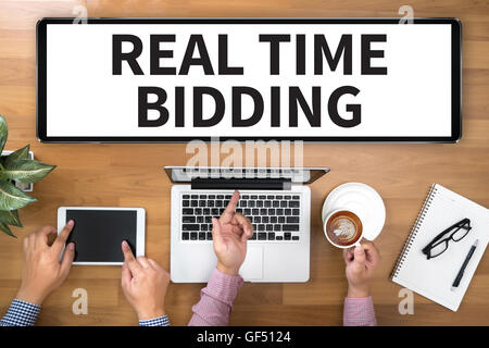 REAL TIME BIDDING Two Businessman working at office desk and using a digital touch screen tablet and use computer, - Stock Photo