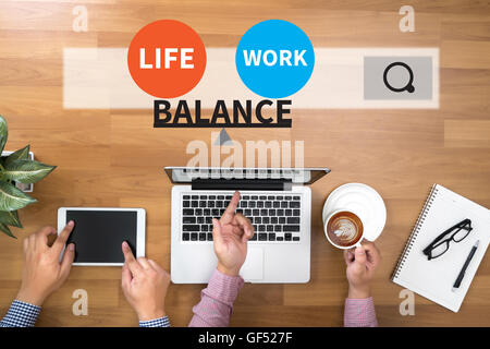 BALANCE Two Businessman working at office desk and using a digital touch screen tablet and use computer - Stock Photo