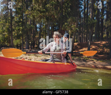 Portrait of happy mature couple having fun at the lake. Woman paddling kayak with man pushing from behind on a summer - Stock Photo