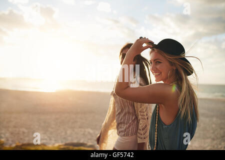 Beautiful friends enjoying a walk on the beach on a sunny day. Two young women walking together on a beach. - Stock Photo