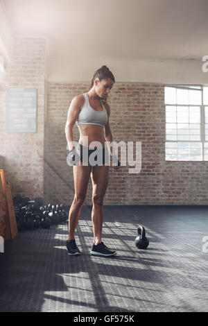 Full length shot of strong young woman in sportswear standing in gym. Tough female athlete at crossfit gym. - Stock Photo