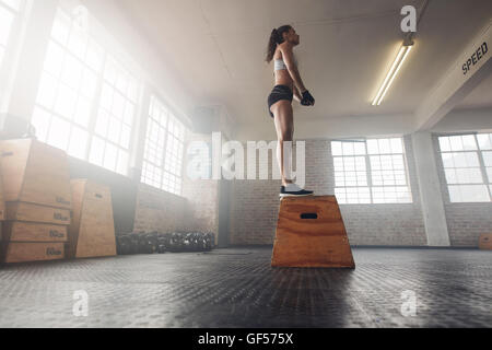 Low angle shot of fit young female model in sports wear standing on a box at gym. Muscular woman doing box jump - Stock Photo