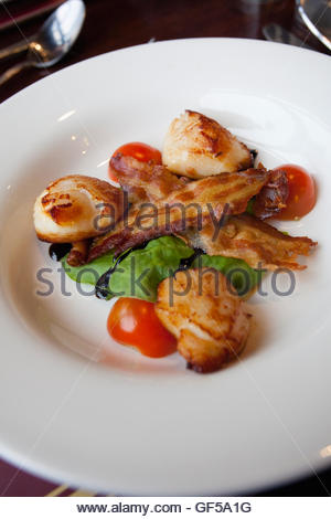 A starter course of hand dived scallops with rashers of crispy bacon and salad served at a restaurant, Isle Of Barra, - Stock Photo