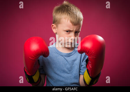 Little boy wearing red boxing gloves - Stock Photo