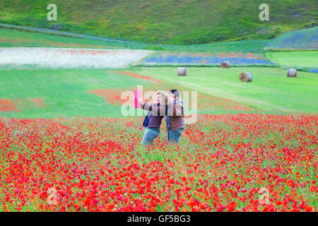 Castelluccio di Norcia, Italy - July 16, 2016: Two girlfriends taking a selfie in a blooming poppy field. In the - Stock Photo