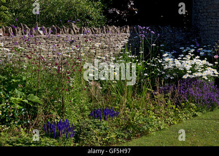 Summer Herbaceous boarder with dry stone wall, Cotswolds,England - Stock Photo