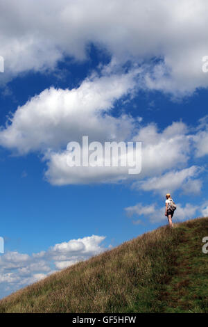 Distant young woman with rucksack, on hillside footpath near Kirkby Stephen in Cumbria,  looking at the view on - Stock Photo