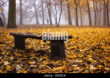 Bench with autumn leafs. In the background lonely man in the park.Warm yellow colors. Foggy calm day in the park. - Stock Photo