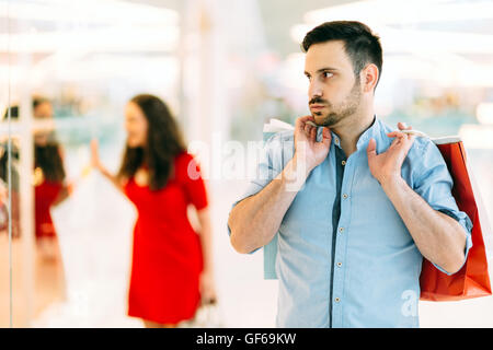 Frustrated man waiting for spouse to finish shopping spree - Stock Photo