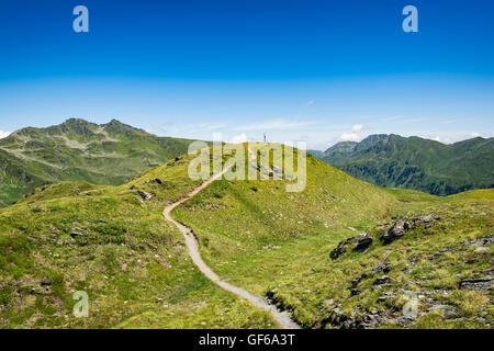 Scenic view over small winding footpath leading to the top of a mountain peak - Stock Photo