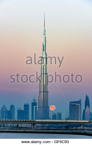 Burj Al Arab and full moon early morning - Stock Photo