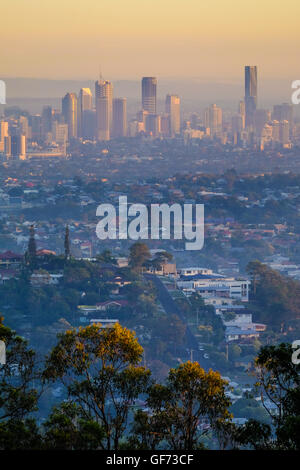 Sunrise over buildings in Brisbane City and southern suburbs from Mt Gravatt lookout - Stock Photo