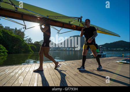 RIO DE JANEIRO - MARCH 22, 2016: After training, Brazilian rowers carry their boat back to the clubhouse at Lagoa. - Stock Photo