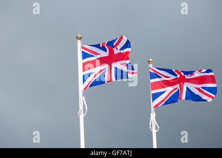 Two Union Jack flags on flag poles blowing in the breeze against stormy grey skies at Dorset in July - Stock Photo