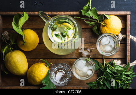 Jug and glasses with homemade lemonade, ice cubes on wooden tray, top view - Stock Photo