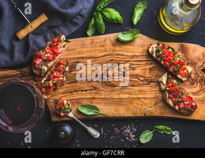 Tomato and basil bruschetta with glass of red wine, olive oil, salt, fresh herbs on wooden board over black background, - Stock Photo