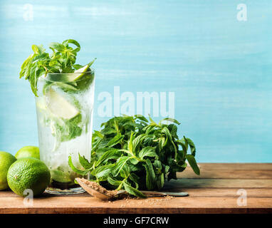 Mojito cocktail in tall glass with mint, brown sugar and limes on a wooden table. Selective focus - Stock Photo