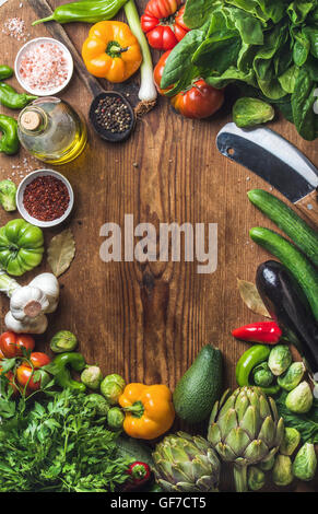 Fresh raw vegetable ingredients for healthy cooking or salad making on wooden background, copy space in center, - Stock Photo