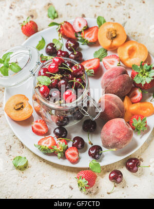 Healthy summer fruit variety. Sweet cherries, strawberries, peaches, apricots and mint leaves on white ceramic serving - Stock Photo