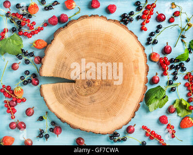 Healthy summer garden berry variety. Black and red currant, gooseberry, rasberry,  strawberry, mint leaves on blue - Stock Photo