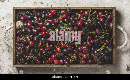 Sweet cherries in rustic wooden tray over light concrete background - Stock Photo