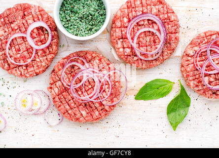 Raw ground beef meat cutlet for cooking burgers with onion rings and spices on white wooden background - Stock Photo