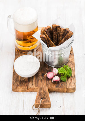Beer snack set. Pint of pilsener in mug, open glass bottle, rye bread croutons with garlic cream cheese sauce and - Stock Photo