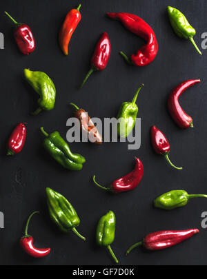 Pattern of small colorful hot chili peppers on black background - Stock Photo