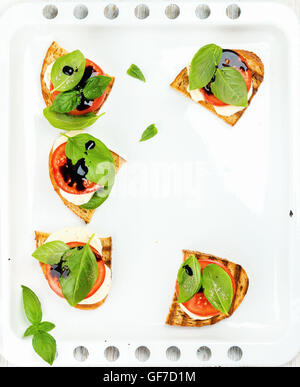 Caprese sandwiches with tomato, mozzarella cheese, basil and balsamic glaze on white baking tray, copy space - Stock Photo