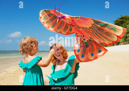 Happy family has fun on sunny sand beach - mother and baby girl walk together along ocean surf and launch traditional - Stock Photo