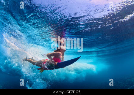 Young active girl wearing bikini in action - surfer with surf board dive underwater under big atlantic ocean wave. - Stock Photo