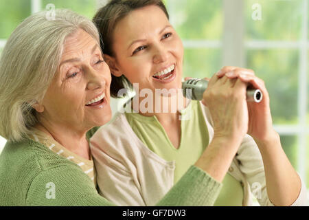Senior woman with daughter  singing on microphone - Stock Photo