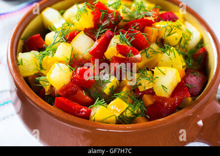 Homemade vegetable stew with yellow zucchini, red peppers, tomatoes in ceramic pot on rustic background - Stock Photo