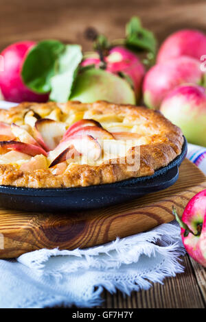 Homemade apple pie cooked in a frying pan and ripe apples on rustic wooden table - Stock Photo